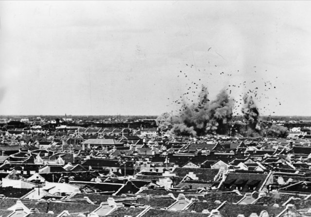 A Japanese bomb drops on brick houses in Chapei on the edge of the International settlement, along which American and British troops are on defence duty during the Second Sino-Japanese War, on October 14, 1937. (Photo by AP Photo)