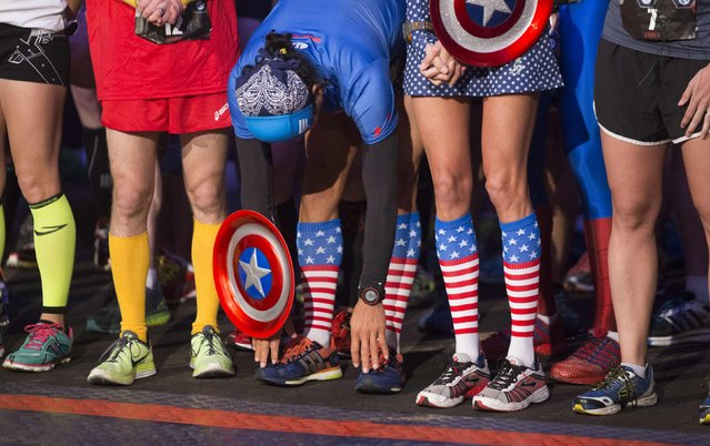 Runners in super hero outfits prepare at the start of the Avengers Super Heroes Half Marathon in and around the Disney Parks in Anaheim, California November 16, 2014. (Photo by Eugene Garcia/Reuters)