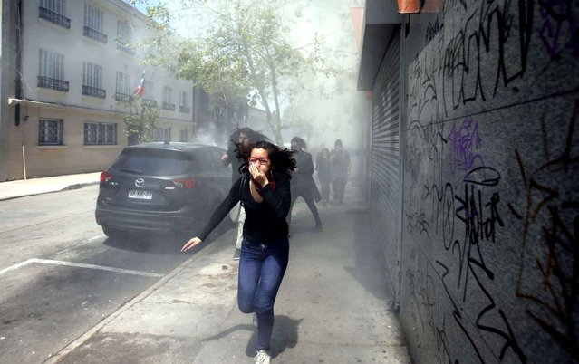 A protester runs from tear gas fired by police at the end of a student march in Santiago, Chile, Thursday, October 15, 2015. Demonstrators marched to complain about delays in an education overhaul and ask President Michelle Bachelet to fulfill her campaign promise of free education. (Photo by Luis Hidalgo/AP Photo)