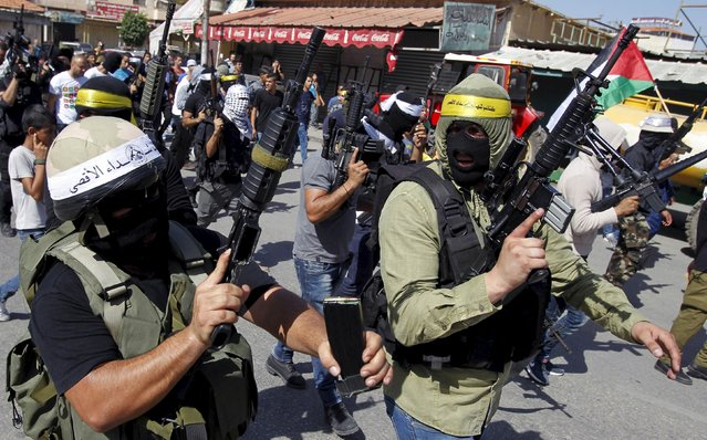 Palestinian militants from Fatah movement take part in an anti-Israeli military show in the West Bank city of Jenin October 16, 2015. The unrest that has engulfed Jerusalem and the occupied West Bank, the most serious in years, has claimed the lives of 35 Palestinians and seven Israelis. The tension has been triggered in part by Palestinians' anger over what they see as increased Jewish encroachment on Jerusalem's al-Aqsa mosque compound, which is also revered by Jews as the location of two destroyed biblical Jewish temples. (Photo by Mohammed Ballas/Reuters)