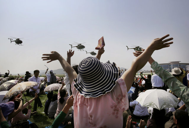 North Koreans wave as Hughes MD-500 helicopters fly past during an aerial display on Saturday, September 24, 2016, in Wonsan, North Korea. North Korea on Saturday opened an air festival featuring sky diving, demonstrations by its air force and lots of beer to promote a newly renovated and upgraded commercial airport in the coastal city of Wonsan that it hopes will draw for foreign tourists. (Photo by Wong Maye-E/AP Photo)