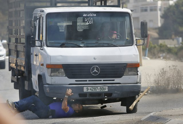 A Palestinian vehicle strikes an Israeli motorist, who died later, in the West Bank city of Hebron October 20, 2015. A Palestinian vehicle ran over and killed an Israeli motorist whom a Reuters photographer said was using a club to hit Palestinian protesters and cars on a roadside in the Israeli-occupied West Bank. (Photo by Mussa Qawasma/Reuters)