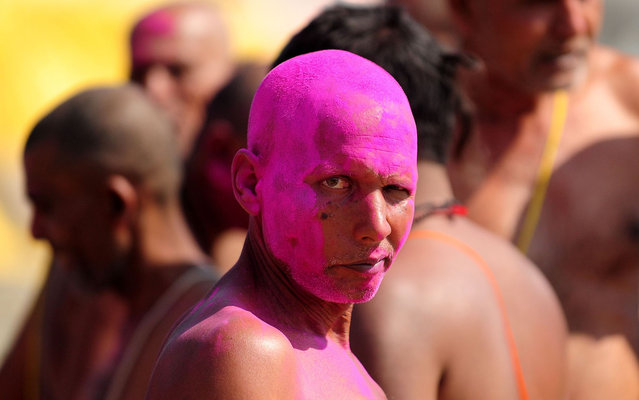 A Bihari Hindu priest, smeared with coloured powder, looks on after the completion of a ritual at the Sangam, the confluence of the rivers Ganges, Yamuna and mythical Saraswati during the Maha Kumbh festival in Allahabad on March 6, 2013. The Kumbh Mela in the town of Allahabad will see up to 100 million worshippers gather over 55 days to take a ritual bath in the holy waters, believed to cleanse sins and bestow blessings. (Photo by Sanjay Kanojia/AFP Photo)