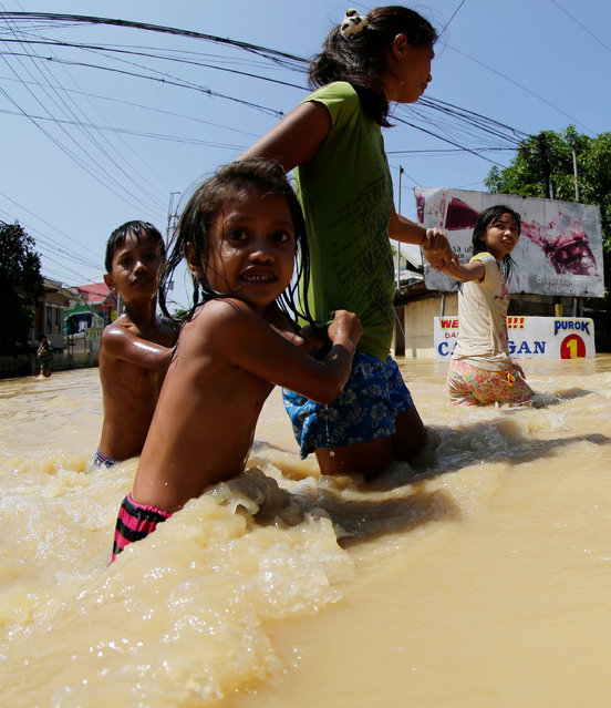 Filipino villagers wade at the flood-hit town of Calumpit, Bulacan province, northern Manila, Philippines, 21 October 2015. (Photo by Francis R. Malasig/EPA)
