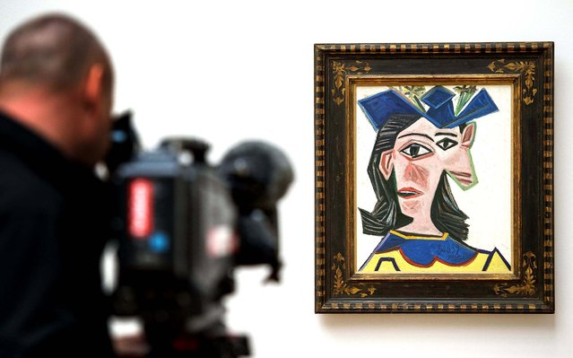 """A man takes pictures of the painting """"Buste de femme au chapeau, Dora"""" (1939) by Pablo Picasso in the Kunstmuseum in Basel, Switzerland, on March 15, 2013. The exhibition """"The Picassos Are Here!"""", a retrospective from Basel collections, lasts from March 17 to July 21. (Photo by Georgios Kefalas/Keystone)"""