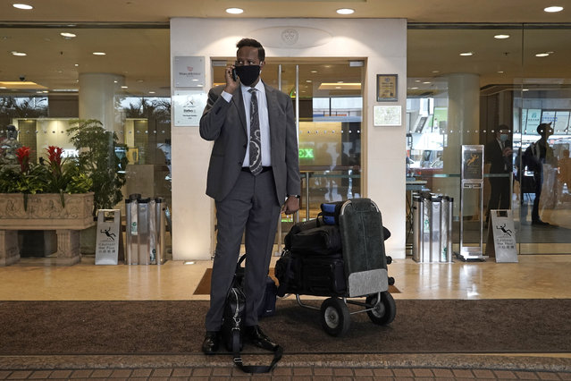 A hotel guest wearing a face mask, waits for transportation after checking out of the Royal Garden Hotel in Hong Kong, Friday, October 9, 2020. The Royal Garden Hotel was evacuating all of its guests after the government confirmed that a waiter who worked at a Vietnamese restaurant at the hotel was found to have the coronavirus COVID-19. (Photo by Kin Cheung/AP Photo)