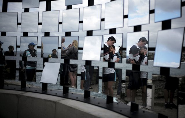 An embracing couple is reflected in multiple mirrors in the artwork entitled 'Half Gate' by Australian artists Matthew Asimakis, Clarence Lee and Caitlin Roseby during the 19th annual Sculptures by the Sea exhibition in Sydney, October 23, 2015. (Photo by Jason Reed/Reuters)