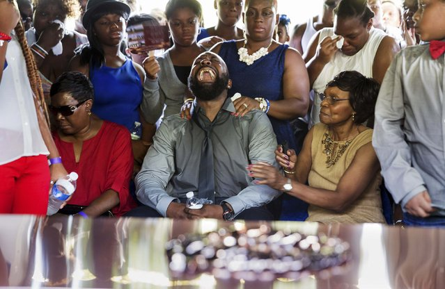 Michael Brown Sr. yells out as his son's casket is lowered into the ground at St. Peter's Cemetery in St. Louis, Missouri, in this August 25, 2014 file photo. (Photo by Richard Perry/Reuters)