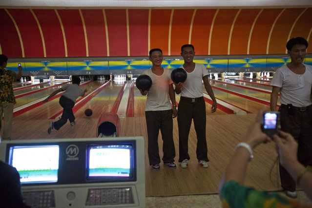 Two North Korean men have their photo taken by a relative after finishing games of bowling at a Pyongyang, North Korea bowling alley on Friday September 7, 2012. (Photo by David Guttenfelder/AP Photo)