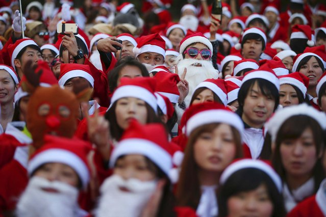 People in Santa Claus costume assemble at the start of Santa Run at Kasai Rinkai Park in Tokyo, Saturday, December 6, 2014. Over 400 people participated in the 2.5 kilometers (1.5 miles) run. (Photo by Eugene Hoshiko/AP Photo)