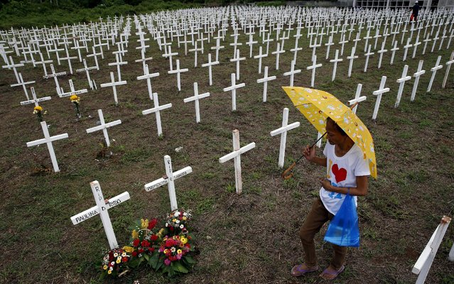 A woman visits the grave of a family member at a mass grave for Typhoon Haiyan victims on All Saints Day in Tacloban city in central Philippines November 1, 2015. (Photo by Erik De Castro/Reuters)