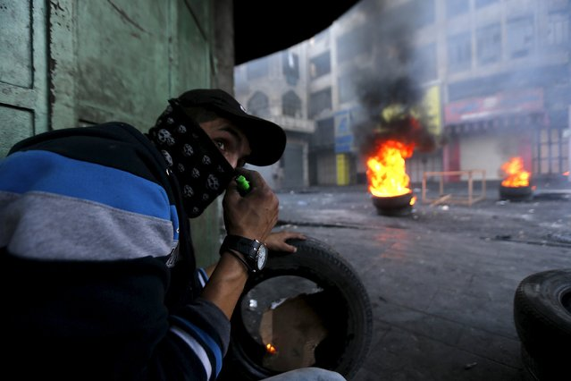 A Palestinian protester takes cover during clashes with Israeli troops in the West Bank city of Hebron October 31, 2015. (Photo by Ammar Awad/Reuters)