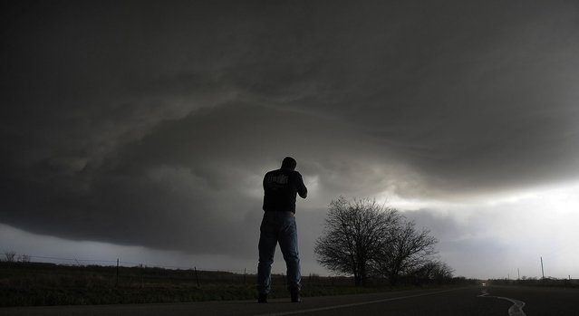 Storm chaser Brad Mack from Buena Park California videotapes a rotating supercell storm west of Newcastle, Texas April 9, 2013. Many of the storms in Tornado Alley that were forecast to be severe this week were taken out by a cold front from Canada. Picture taken April 9, 2013. (Photo by Gene Blevins/Reuters)