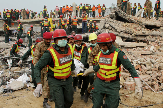 Pakistani rescue workers carry a body of a victim in Lahore, Pakistan, Friday, November 6, 2015. A spokesman for a Pakistani rescue agency says hopes are starting to fade for finding more survivors in the rubble of a four-story factory which collapsed this week killings dozens of people left many injured. (Photo by K. M. Chaudary/AP Photo)