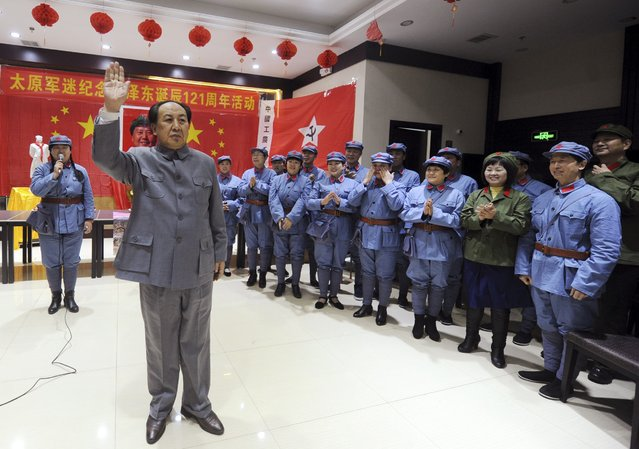 Ren Zhenlong (front), an impersonator of China's late Chairman Mao Zedong, waves next to people dressed as Red Army soldiers during a performance to celebrate the upcoming 121st anniversary of Mao's birth, in Taiyuan, Shanxi province, December 13, 2014. (Photo by Reuters/Stringer)