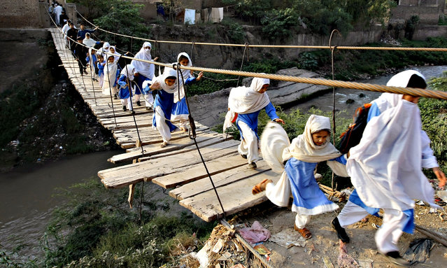 Pakistani students cross a makeshift bridge in Peshawar, Pakistan, Tuesday, October 6, 2015. The previous bridge was washed away in a flood. (Photo by Mohammad Sajjad/AP Photo)