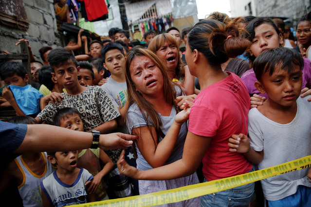Janeth Mejos (C) reacts as the body of her father Paquito Mejos is taken out of their home shortly after he was killed in a police operation in Manila, Philippines October 14, 2016. (Photo by Damir Sagolj/Reuters)
