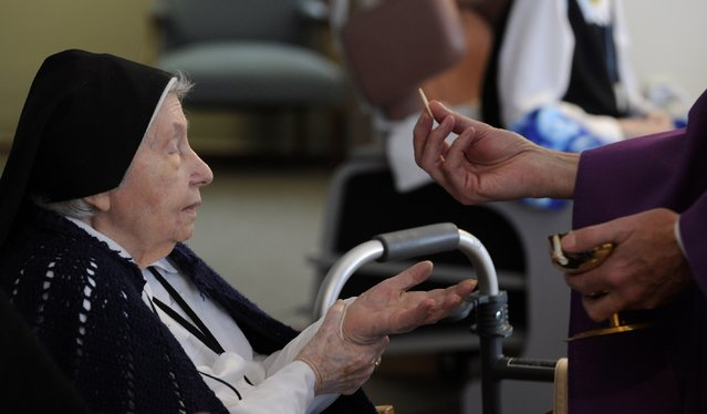 Sister Mary Stella Cunniff receives the Eucharist during services at Our Lady of Rickenbach health care facility that is part of the Benedictine Sisters of Perpetual Adoration monastery in Clyde Missouri December 18, 2014. (Photo by Dave Kaup/Reuters)