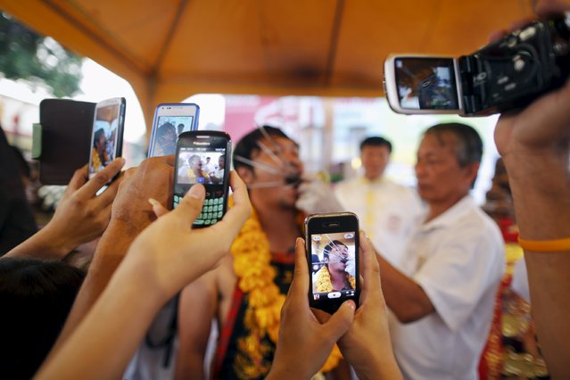People take pictures as a devotee of the Chinese Bang Neow Shrine is helped with piercing before a street procession during the annual vegetarian festival in Phuket in this October 20, 2012 file photo. Thailand's telecoms regulator is expecetd to hold a 4G auction on November 11, 2015. (Photo by Damir Sagolj/Reuters)
