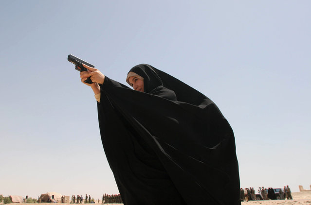 In this June 25, 2008 file photo, a female police officer aims with her pistol in a shooting range, during a graduation ceremony in Karbala, 80 kilometers (50 miles) south of Baghdad, Iraq. Some 115 police woman graduated from Karbala's police academy. (Photo by Ahmed Alhussainey/AP Photo)