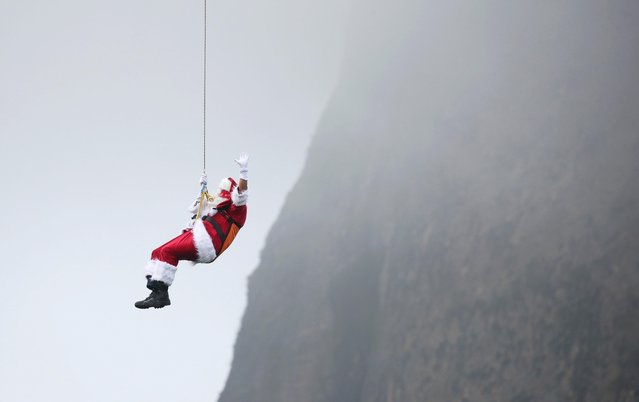 A man dressed as Santa Claus rappels from a cable car while descending from the Pao de Acucar Mountain (Sugar Loaf Mountain) during his arrival to a Christmas event in Rio de Janeiro, Brazil on December 5, 2020. (Photo by Ricardo Moraes/Reuters)