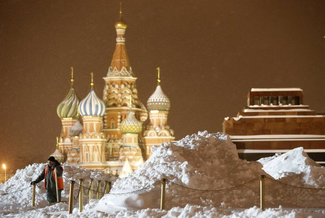 A worker rests as he clears and removes snow in Red Square, with St. Basil's Cathedral (L) and the mausoleum of Soviet state founder Vladimir Lenin seen in the background, in central Moscow, December 25, 2014. (Photo by Sergei Karpukhin/Reuters)