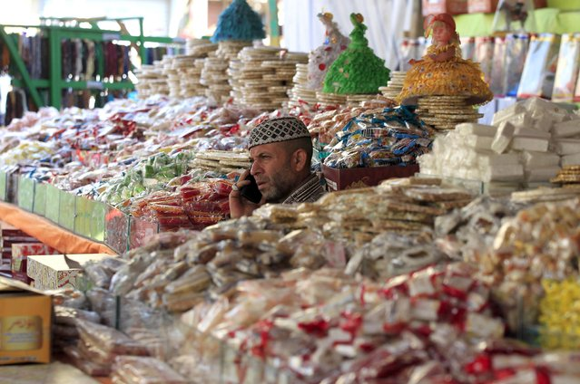 "A man sells traditional sweets for children to celebrate the birthday of prophet Muhammad, also known as ""mawlid al nabi"", which will fall next week, in a makeshift tent in Cairo, December 30, 2014. (Photo by Mohamed Abd El Ghany/Reuters)"