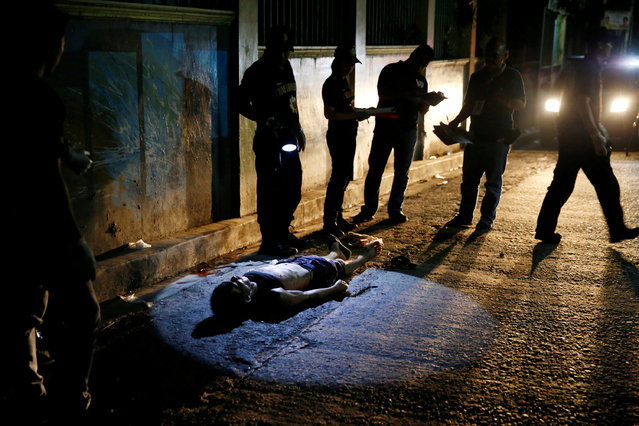 Police investigate the body of Herman Cunanan, whom police said was killed by men riding in two motorcycles, in Quezon city, Metro Manila, Philippines October 19, 2016. Cunanan was a drug user, his unidentified live-in partner told reporters. (Photo by Erik De Castro/Reuters)
