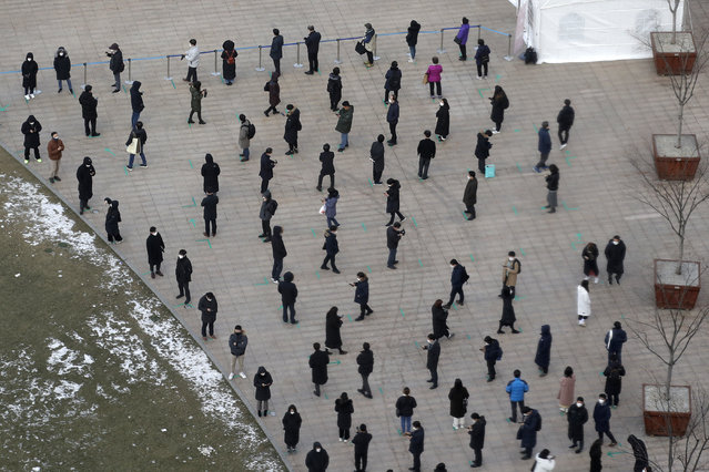 People queue in line to wait for coronavirus testing while maintaining social distancing at Seoul Plaza in Seoul, South Korea, Friday, December 18, 2020. (Photo by Lee Jin-man/AP Photo)