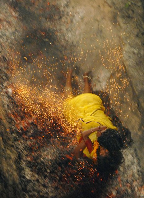 An Indian Hindu devotee falls on burning coals while holding her daughter during a coal run at the Maa Maariamma Mela in Jalandhar, India. The devotees run on fire after fasting for seven days to prove their devotion. The mother and daughter were both injured. (Photo by Shammi Mehra/AFP Photo)