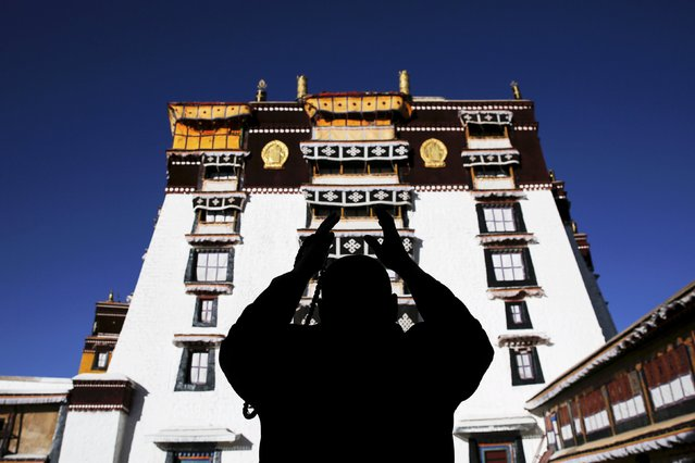 A Tibetan man prays at the Potala Palace in Lhasa, Tibet Autonomous Region, China November 17, 2015. The Potala Palace, once the seat of Tibetan government and traditional residence of Dalai Lama, is a 13-storey palace with more than 1000 rooms. More than 1,300 years old, the palace is more than 3,700 meters above sea level and is a UNESCO World Heritage site. (Photo by Damir Sagolj/Reuters)