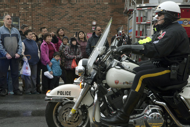 Onlookers stand to the side as motorcycle riding police officers lead the procession route during the funeral of New York Police Department Officer Wenjian Liu, Sunday, January 4, 2015. (Photo by John Minchillo/AP Photo)