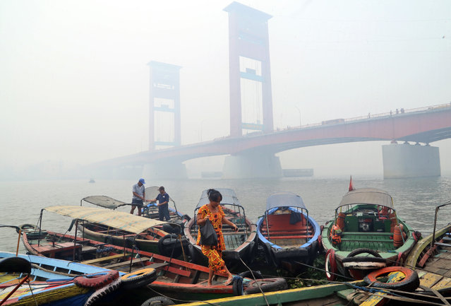 In this September 29, 2015 file photo, a woman disembarks from a boat as the Ampera Bridge is shrouded in haze from wildfires in Palembang, South Sumatra, Indonesia. Indonesian, Malaysian and Singaporean authorities have dismissed research that smoky haze from catastrophic forest fires in Indonesia last year caused 100,000 deaths. Some even contend the haze caused no serious health problems, but experts say those assertions contradict well-established science. Others say governments should not dismiss the study even if the estimated deaths are arguable. (Photo by AP Photo)