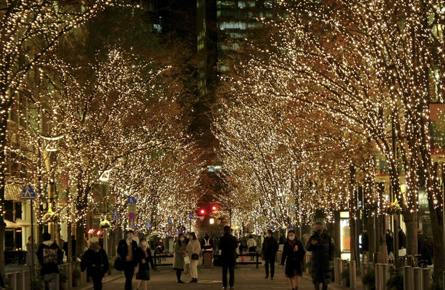 """People walk under winter-themed illumination, lit by approximately 1.2 million """"champagne gold"""" LED lights as part of seasonal decorations, in the Marunouchi business district of Tokyo on December 21, 2020. (Photo by Kazuhiro Nogi/AFP Photo)"""