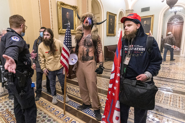 Supporters of President Donald Trump are confronted by Capitol Police officers outside the Senate Chamber inside the Capitol, Wednesday, January 6, 2021 in Washington. (Photo by Manuel Balce Ceneta/AP Photo)