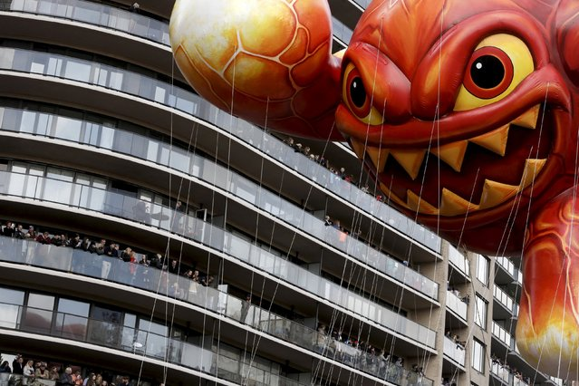 "The ""Skylanders Eruptor"" balloon moves by people on balconies during the 89th Macy's Thanksgiving Day Parade in the Manhattan borough of New York, November 26, 2015. (Photo by Andrew Kelly/Reuters)"