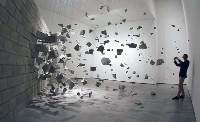 A visitor takes pictures of an installation representing an exploding wall by Cuban artists Dagoberto Rodriguez and Marco Castillo during an exhibit at Es Baluard museum in Palma de Mallorca, on the Spanish Balearic islands, October 17, 2011. (Photo by Enrique Calvo/Reuters)