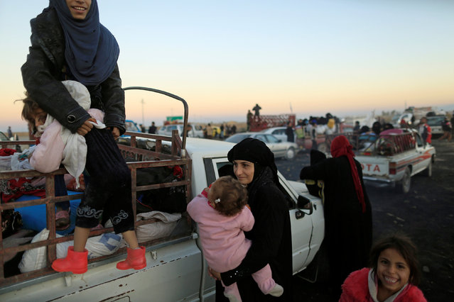 A woman who had just fled Kokjali near Mosul carries her child as she arrives with her family at a Peshmerga checkpoint east of Mosul, Iraq November 3, 2016. (Photo by Zohra Bensemra/Reuters)