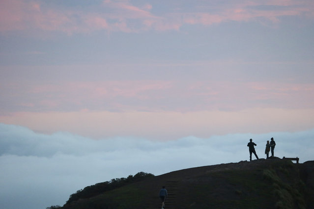 Visitors stand atop a hill as fog rolls in from a view on Twin Peaks on Friday, January 9, 2015, in San Francisco. (Photo by Marcio Jose Sanchez/AP Photo)