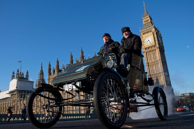 """A vintage car is driven past the Houses of Parliament in Westminster shortly after beginning the 120th """"Veteran Car Run"""" from Hyde Park in London, to Brighton in southern England, on November 6, 2016. Around 600 classic cars took part in the annual 60 mile journey to the south coast resort. (Photo by Justin Tallis/AFP Photo)"""