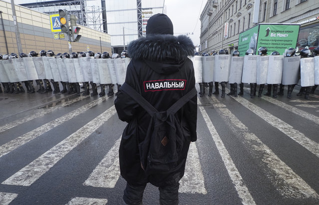 """A man with a sign """"Navalny"""" on his back stands in front of riot policemen blocking the way to protester during a protest against the jailing of opposition leader Alexei Navalny in St. Petersburg, Russia, Sunday, January 31, 2021. (Photo by Dmitri Lovetsky/AP Photo)"""
