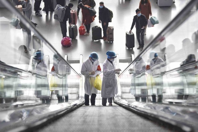 Staff members of the Chengdu center for disease control under the China Railway Chengdu Bureau Group Co., Ltd. collect environmental samples for COVID-19 test at an escalator of the east railway station in Chengdu, southwest China's Sichuan Province, February 2, 2021. (Photo by Xinhua News Agency/Rex Features/Shutterstock)