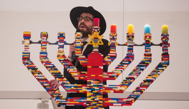 Rabbi Shmuel Havlin sings atop a ladder in front of Hanukkah candles made out of Lego blocks in the hall of the Joseph-Carlebach school in Hamburg, Germany, December 9, 2015. According to the Jewish educational center, students have built the world's highest Hanukkah Menorah from 30,000 Lego blocks. The newly built Hanukkah Menorah is 5.82 meters high. (Photo by Christian Charisius/dpa via AP Photo)