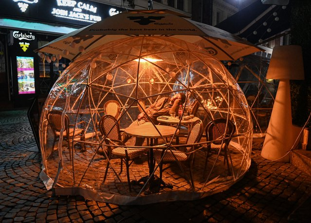 A man sleeps inside a protection bubble, used by a pub for its customers as part of coronavirus social distancing measures, during a newly-instated curfew in Bucharest late on November 9, 2020. The Romanian government imposed the 30-day nationwide curfew starting November 9, with people's movements prohibited between 11pm and 5am, with exceptions such as professional interest or medical assistance, and mandatory mask-wearing in all public spaces. Romania reported a record 10,260 new COVID-19 cases on November 6, the highest single-day increase to date in the eastern European countries. (Photo by Daniel Mihailescu/AFP Photo)