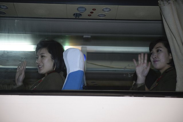 Members of Moranbong Band from North Korea wave from inside a bus after a rehearsal session at the National Grand Theatre in Beijing, China, December 11, 2015. (Photo by Reuters/Stringer)
