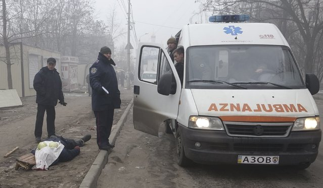 An ambulance of the Ukrainian forces stops along a street beside the body of a victim killed by a recent shelling of a residential sector in Mariupol, eastern Ukraine, January 24, 2015. (Photo by Nikolai Ryabchenko/Reuters)