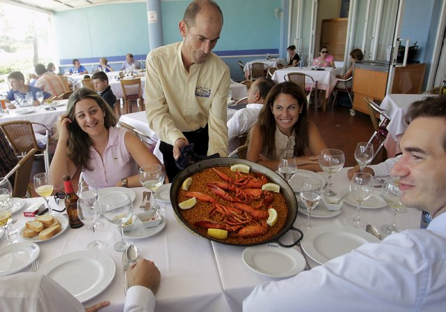 A waiter serves a traditional paella at a beach-side restaurant in Valencia, Spain in this July 24, 2014 file photo. Spain is expected to report its latest unemployment figures this week. (Photo by Heino Kalis/Reuters)