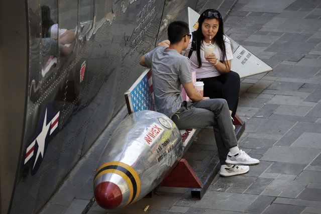 A Chinese couple drink on a bench in a shape of a mocked aerial bomb with a U.S. flag outside a fashion boutique selling U.S. brand clothing at a mall in Beijing, Thursday, June 28, 2018. China's government defended its trade record as a benefit to the world in a new effort Thursday to defuse U.S. and European pressure over market access and technology policy. (Photo by Andy Wong/AP Photo)