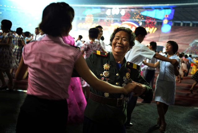 North Korean veteran Oh Gyu Sun, 78, who was a nurse in the Korean War, participates in a mass dance party during North Korean celebrations marking the 60th anniversary of the Korean War armistice, in Pyongyang, on July 28, 2013. (Photo by Wong Maye-E/Associated Press)
