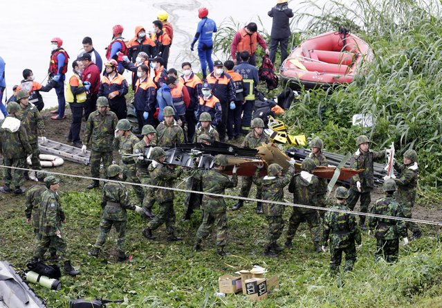 Rescuers and soldiers remove airplane parts after a TransAsia plane crashed into a river in New Taipei City, February 4, 2015. (Photo by Pichi Chuang/Reuters)